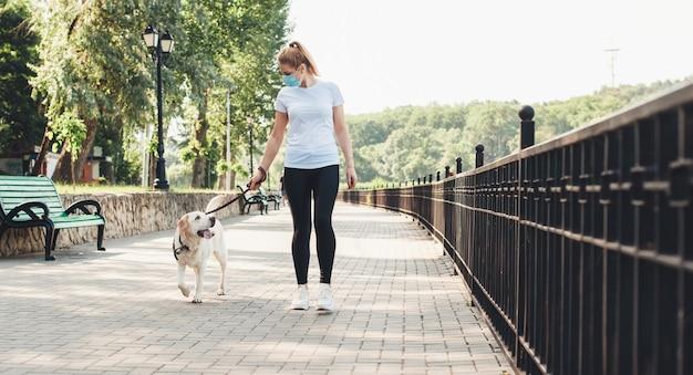 Blonde frau und ihr hund gehen im park, während sie eine medizinische maske auf gesicht während des coronavirus tragen