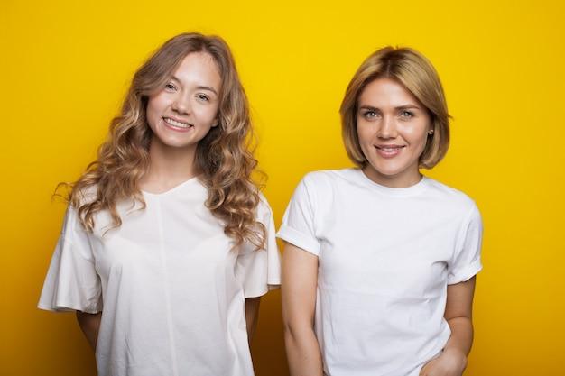 Blonde frau und ihre lockige schwester lächeln in der gleichen kleidung an einer gelben studiowand in die kamera