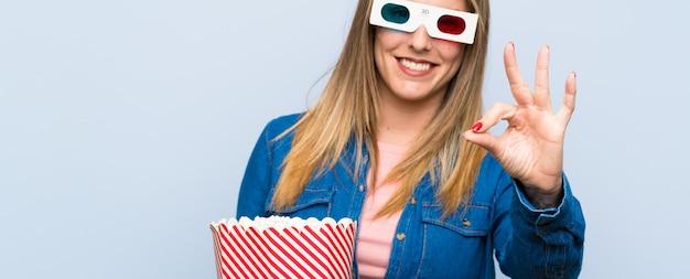 Blonde frau, welche die popcorn zeigt ein okayzeichen mit den fingern isst
