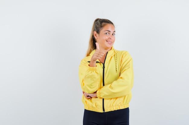 Blonde frau zeigt daumen hoch in gelber bomberjacke und schwarzer hose und sieht optimistisch aus, vorderansicht.