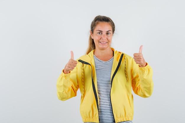 Blonde frau zeigt daumen hoch mit beiden händen in gelber bomberjacke und gestreiftem hemd und sieht hübsch aus