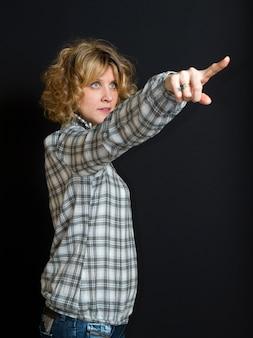Blonde frau zeigt einen punkt mit ihrem finger