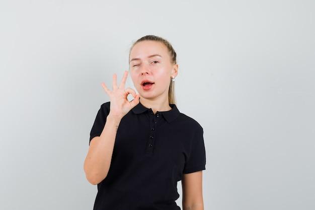 Blonde frau zeigt ok zeichen und zwinkert im schwarzen t-shirt und sieht optimistisch aus