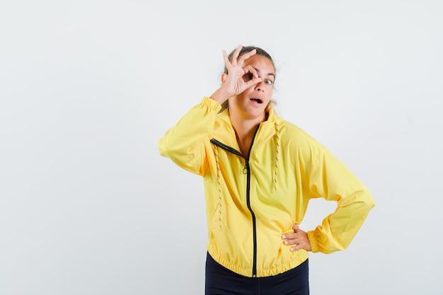 Blonde frau zeigt okay zeichen auf auge und legt hand auf taille in gelber bomberjacke und schwarzer hose und sieht überrascht aus