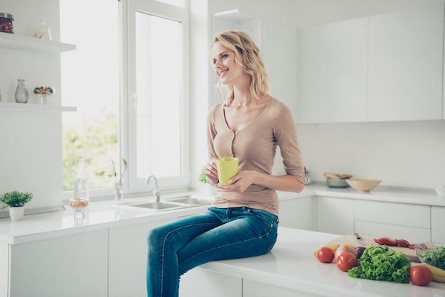 Blonde frau zu hause in der küche mit gemüse