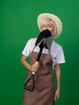 Blonde gärtnerin mittleren alters in uniform mit hut, der von hinten spaten hält