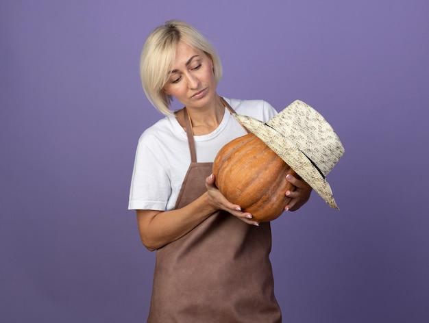 Blonde gärtnerin mittleren alters in uniform mit hut, die butternut-kürbis mit hut darauf hält und betrachtet