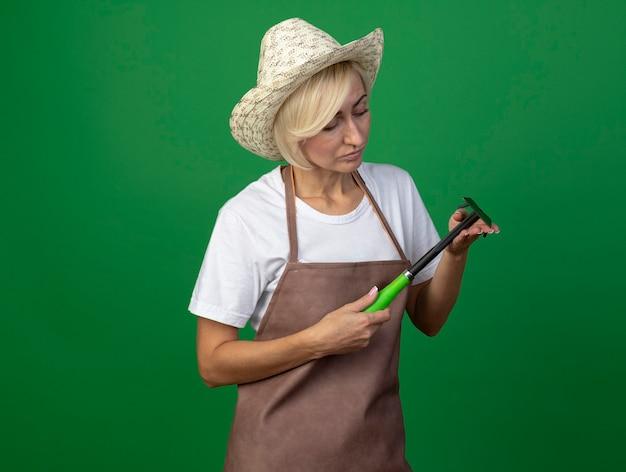 Blonde gärtnerin mittleren alters in uniform mit hut, die hacke hält und betrachtet