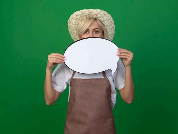 Blonde gärtnerin mittleren alters in uniform mit hut, die sprechblase von hinten hält