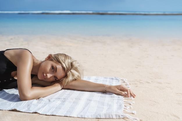 Blonde gebräunte frau liegen stranddecke in der nähe von ozeanufer.