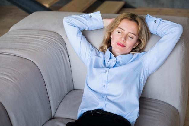 Blonde geschäftsfrau, die auf couch schläft