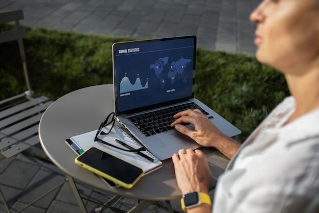 Blonde geschäftsfrau, die draußen an ihrem laptop arbeitet