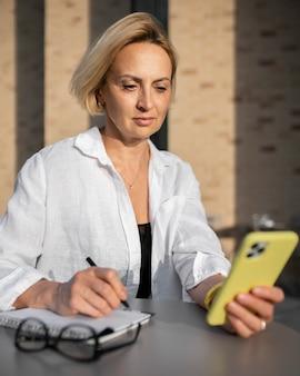 Blonde geschäftsfrau, die ihr telefon überprüft