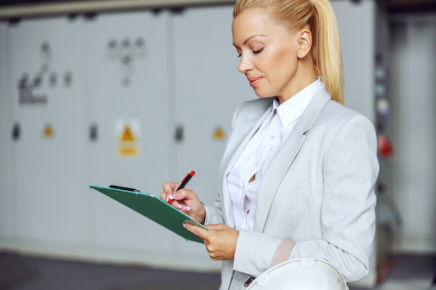 Blonde geschäftsfrau, die im heizwerk steht, zwischenablage hält und maschinen überprüft.