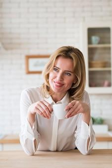 Blonde geschäftsfrau, die mit kaffeetasse sitzt