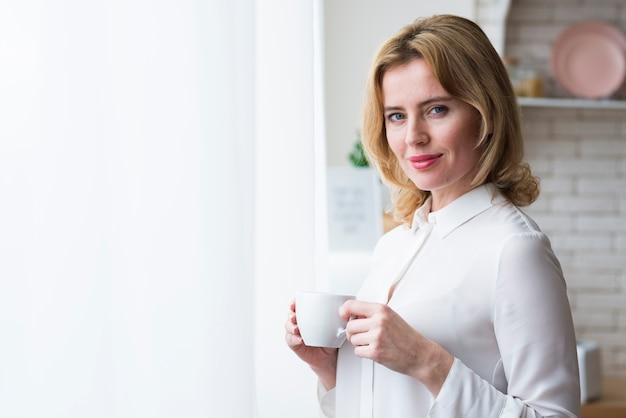 Blonde geschäftsfrau, die mit kaffeetasse steht