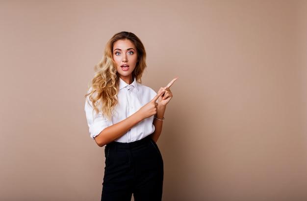 Blonde geschäftsfrau, die oben zeigt und auf beige wand schaut. tragen sie stilvolle arbeitskleidung. kopieren sie den text. überraschungsgesicht.
