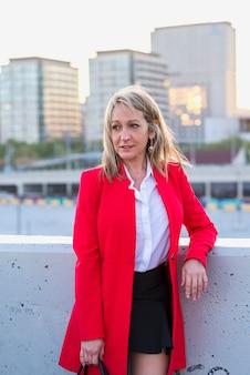 Blonde geschäftsfrau, die rote jacke und schwarzes hemd trägt, die in der stadt stehen, während wegsehen