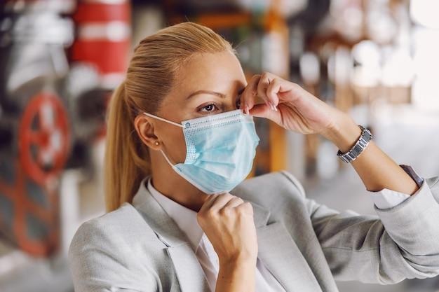 Blonde geschäftsfrau im anzug, die gesichtsmaske beim stehen in ihrer pflanze während des koronavirus setzt.