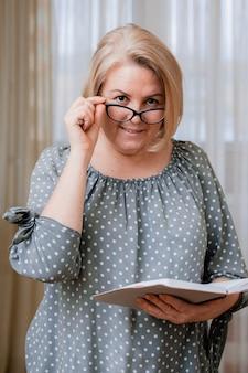 Blonde geschäftsfrau, lächelnd und älter, trägt eine brille, liest und stöbert mit einem tagesplaner und einem kugelschreiber. porträt eines schönen gepflegten rentners 50-60 jahre alt im zimmer.