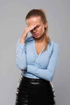 Blonde geschäftsfrau mit starken kopfschmerzen