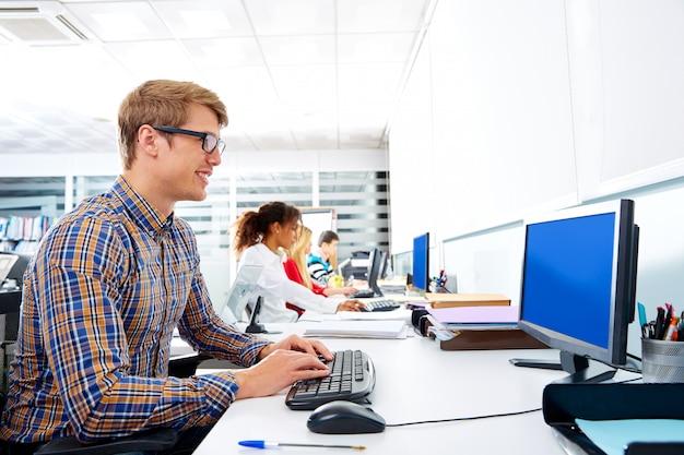 Blonde geschäftsmannjunge im büro mit computer