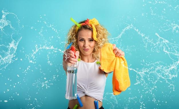Blonde hausfrau spritzt desinfektionsmittel, um viren und bakterien cyan hintergrund zu entfernen