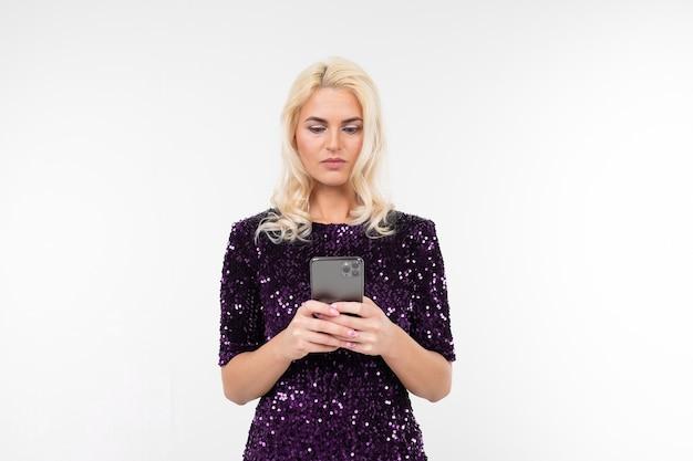 Blonde hübsche dame, die ein telefon in ihren händen mit kopienraum hält