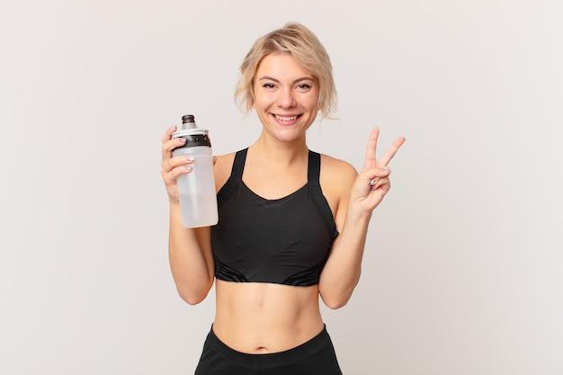 Blonde hübsche fitnessfrau mit einer wasserflasche