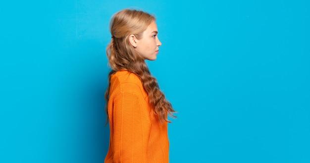 Blonde hübsche frau auf profilansicht, die raum voraus kopiert, denkt, sich vorstellt oder träumt