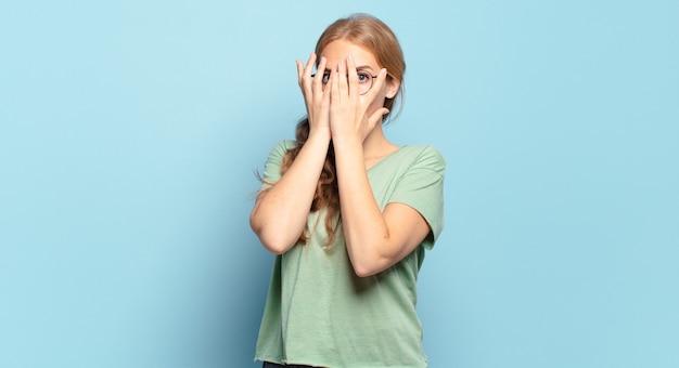 Blonde hübsche frau, die angst oder verlegenheit hat, späht oder ausspioniert mit halb mit händen bedeckten augen