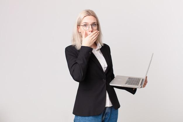 Blonde hübsche frau, die den mund mit den händen mit einem schockierten bedeckt und einen laptop hält