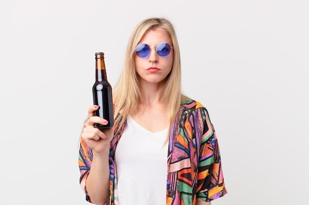 Blonde hübsche frau, die ein bier trinkt. sommerkonzept
