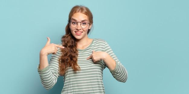 Blonde hübsche frau, die glücklich, überrascht und stolz ist und mit einem aufgeregten, erstaunten blick auf sich selbst zeigt