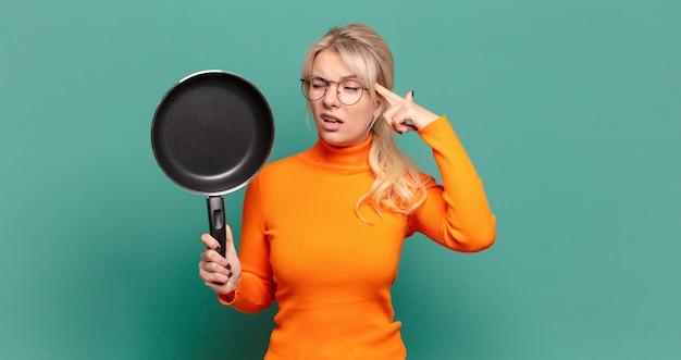 Blonde hübsche frau, die koch mit einer pfanne lernt