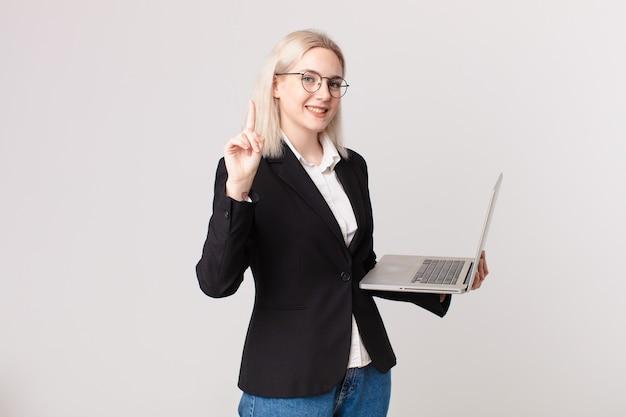 Blonde hübsche frau, die lächelt und freundlich aussieht, nummer eins zeigt und einen laptop hält