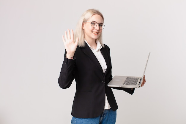 Blonde hübsche frau, die lächelt und freundlich aussieht, nummer fünf zeigt und einen laptop hält