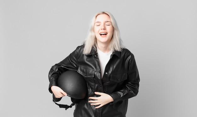 Blonde hübsche frau, die laut über irgendeinen urkomischen witz lacht. motorradfahrerkonzept