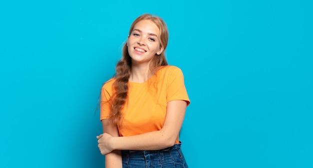 Blonde hübsche frau, die schüchtern und fröhlich lacht, mit einer freundlichen und positiven, aber unsicheren einstellung