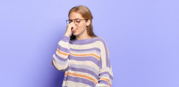 Blonde hübsche frau, die sich angewidert fühlt und die nase hält, um einen üblen und unangenehmen gestank zu vermeiden