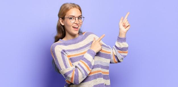 Blonde hübsche frau, die sich freudig und überrascht fühlt, mit einem schockierten ausdruck lächelt und zur seite zeigt