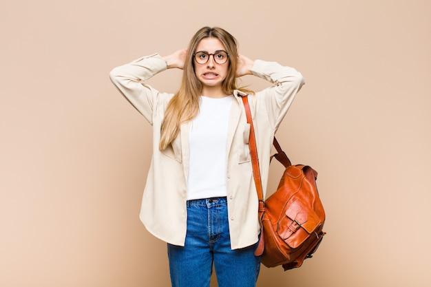 Blonde hübsche frau, die sich gestresst, besorgt, ängstlich oder verängstigt fühlt, mit den händen auf dem kopf und in panik über fehler