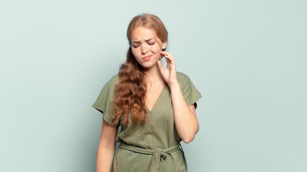 Blonde hübsche frau, die sich gestresst, frustriert und müde fühlt, sich den schmerzenden nacken reibt, mit einem besorgten, unruhigen blick