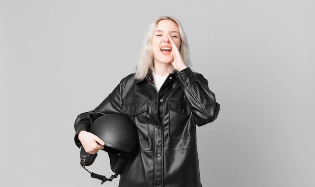 Blonde hübsche frau, die sich glücklich fühlt und mit den händen neben dem mund einen großen schrei ausstößt. motorradfahrerkonzept