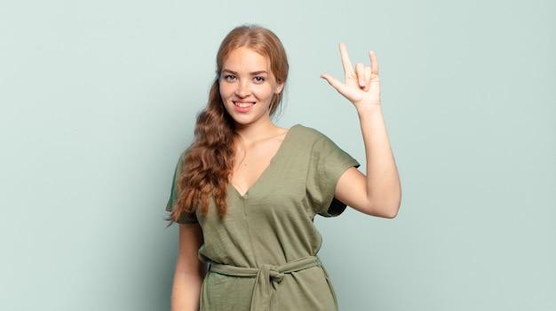 Blonde hübsche frau, die sich glücklich, lustig, selbstbewusst, positiv und rebellisch fühlt und mit der hand rock- oder heavy-metal-zeichen macht