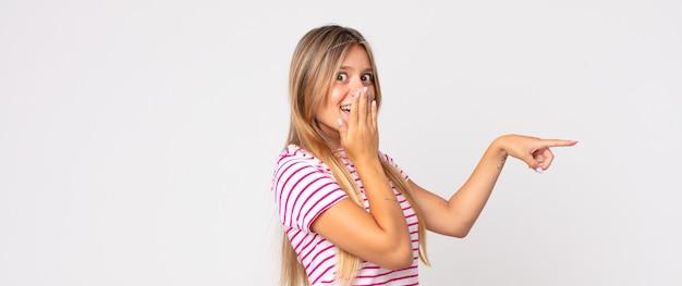 Blonde hübsche frau, die sich glücklich, schockiert und überrascht fühlt, den mund mit der hand bedeckt und auf den seitlichen kopierraum zeigt