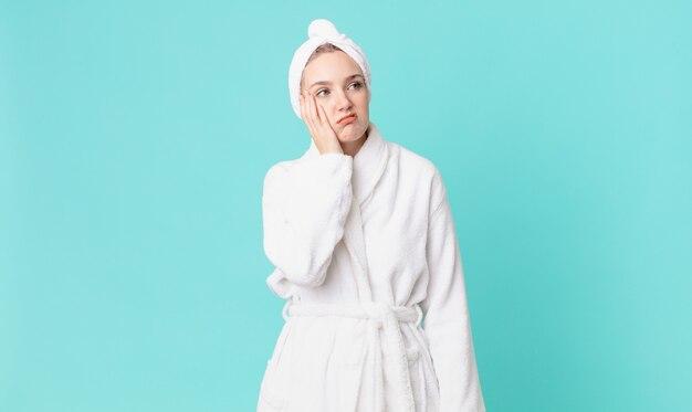 Blonde hübsche frau, die sich nach einem ermüdenden und tragenden bademantel gelangweilt, frustriert und schläfrig fühlt