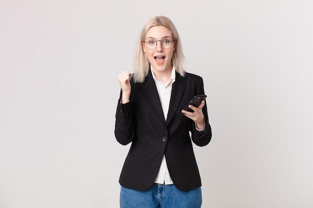 Blonde hübsche frau, die sich schockiert fühlt, lacht und erfolg feiert und ein mobiltelefon hält