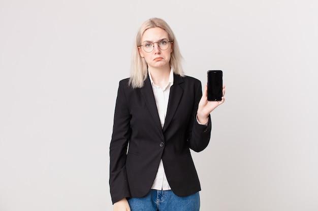 Blonde hübsche frau, die sich traurig und weinerlich mit einem unglücklichen blick fühlt und weint und ein mobiltelefon hält