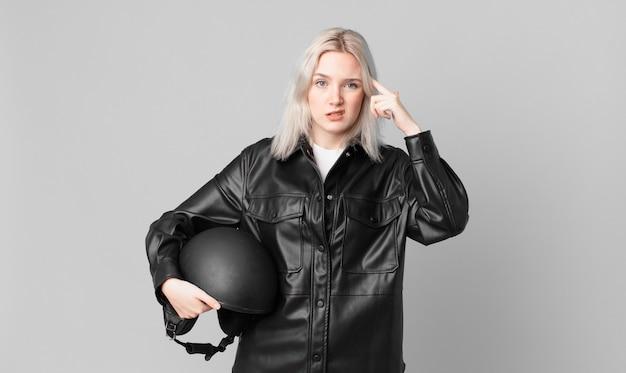 Blonde hübsche frau, die sich verwirrt und verwirrt fühlt und zeigt, dass sie verrückt sind. motorradfahrerkonzept